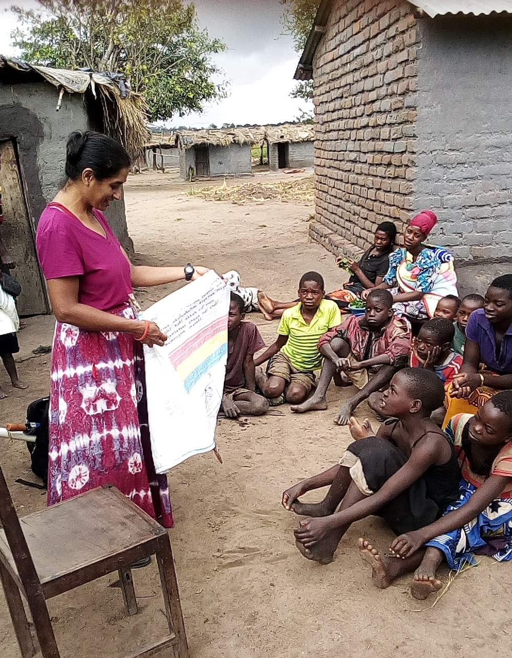 Vishakha Wavde holding maize sack in village in Malawi