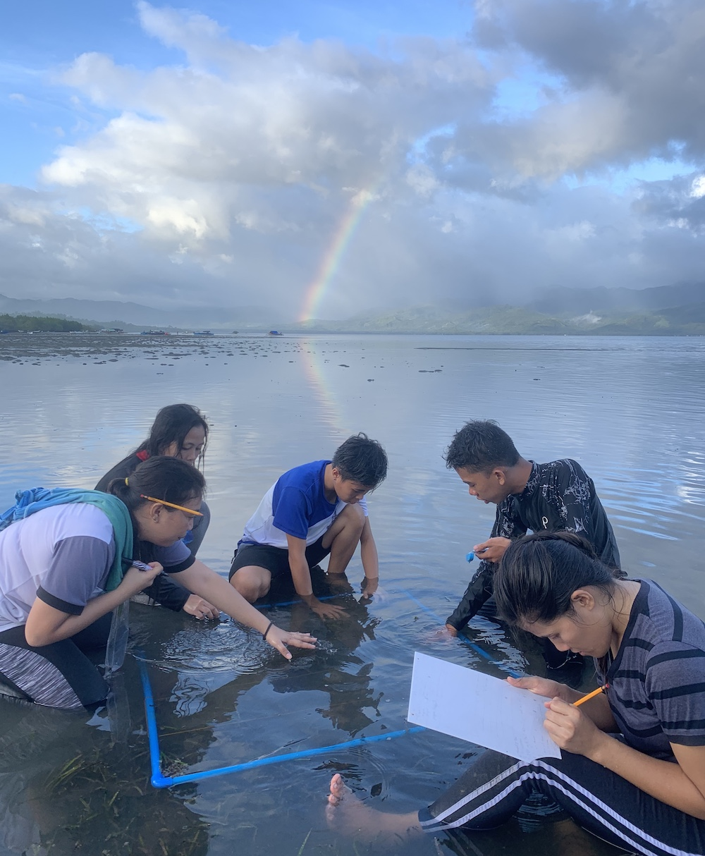 Students in the Philippines conduct seagrass survey in water