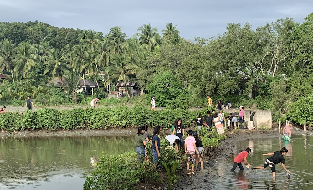 Students in the Philippines remove debris from fishponds