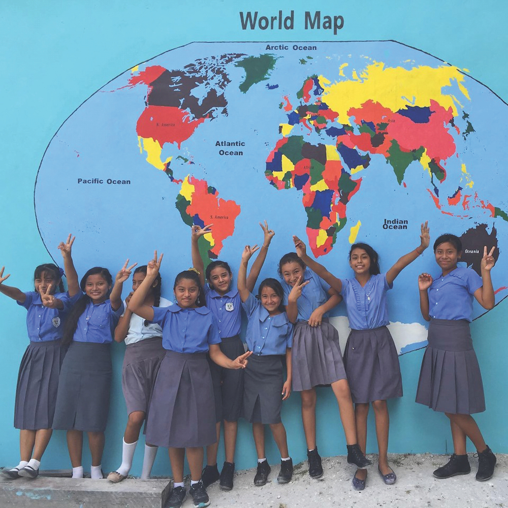 Shoolgirls in Belize with world map painting
